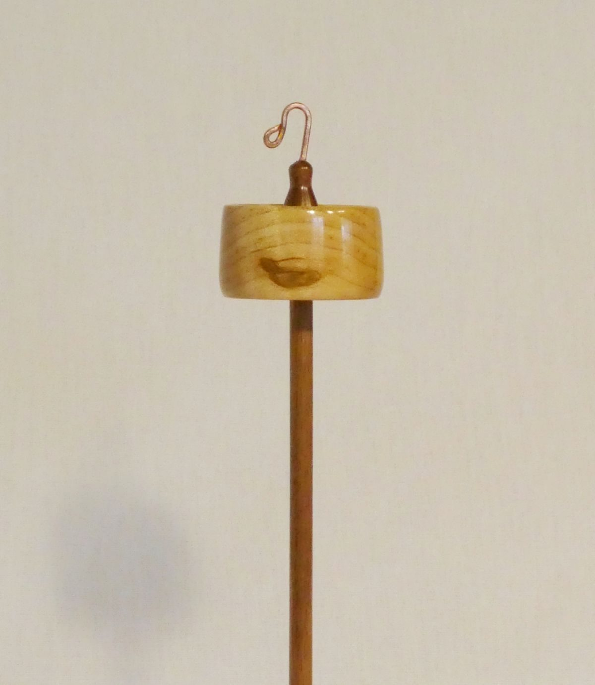 Quilted Maple and Black Walnut wood top whorl drop spindle. Whorl is rim weighted and notched for a long easy spin. Learn how to spin yarn from Cynthia D. Haney