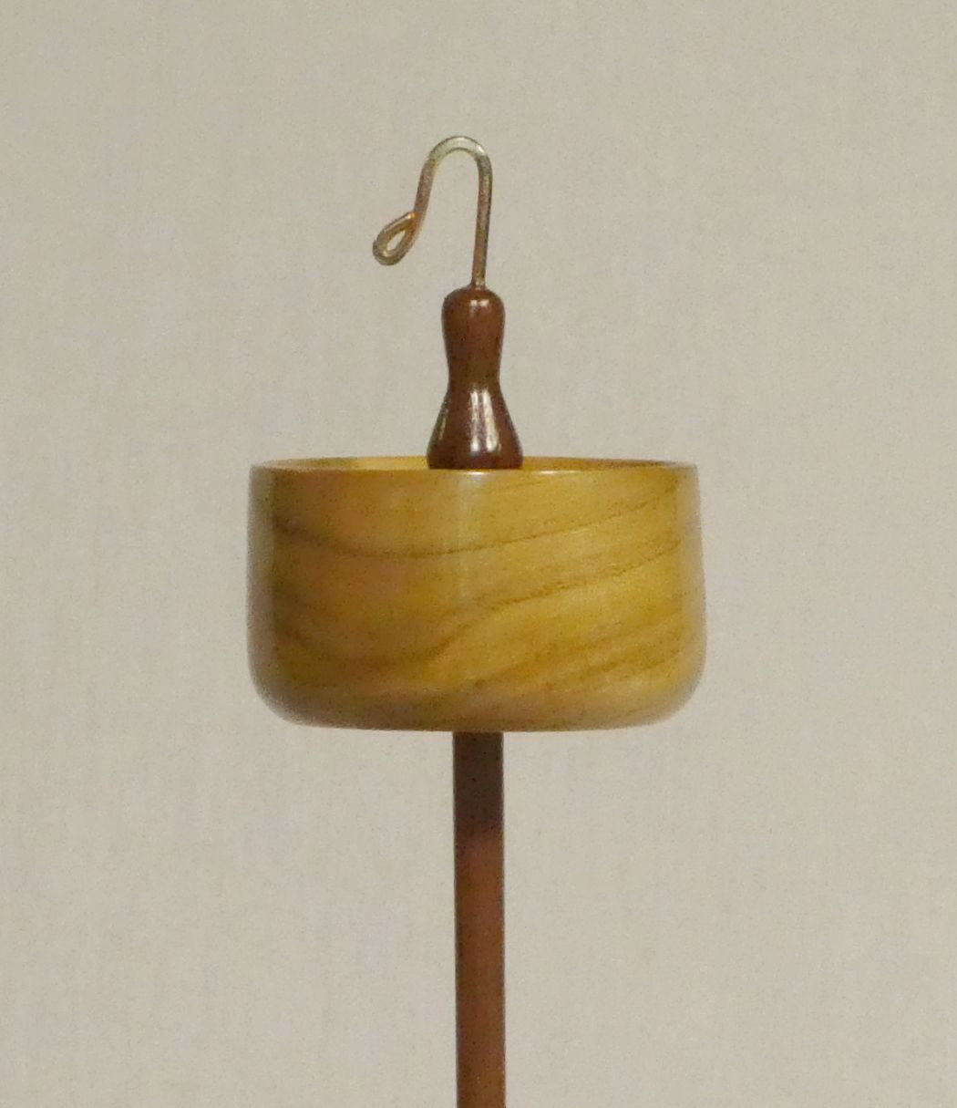 Tulip Poplar and Black Walnut top whorl drop spindle mid weight handmade by Cynthia D. Haney. This one of a kind heirloom high whorl spindle is rim weighted and notched with a hook. Easy to use when learning how to spin yarn.