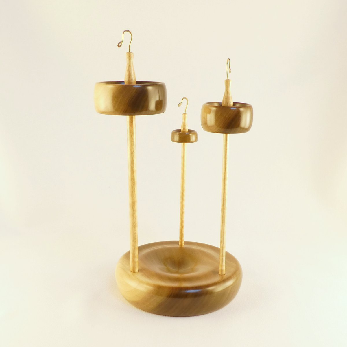 Set of three top whorl drop spindles with a matching holder, storage, display stand. Designed and handmade by Cynthia D. Haney with rim weighted notched whorls in Tulip Poplar with remarkable contrasting colored grain. Shafts are hand turned curly ash wood, hooks bronze.