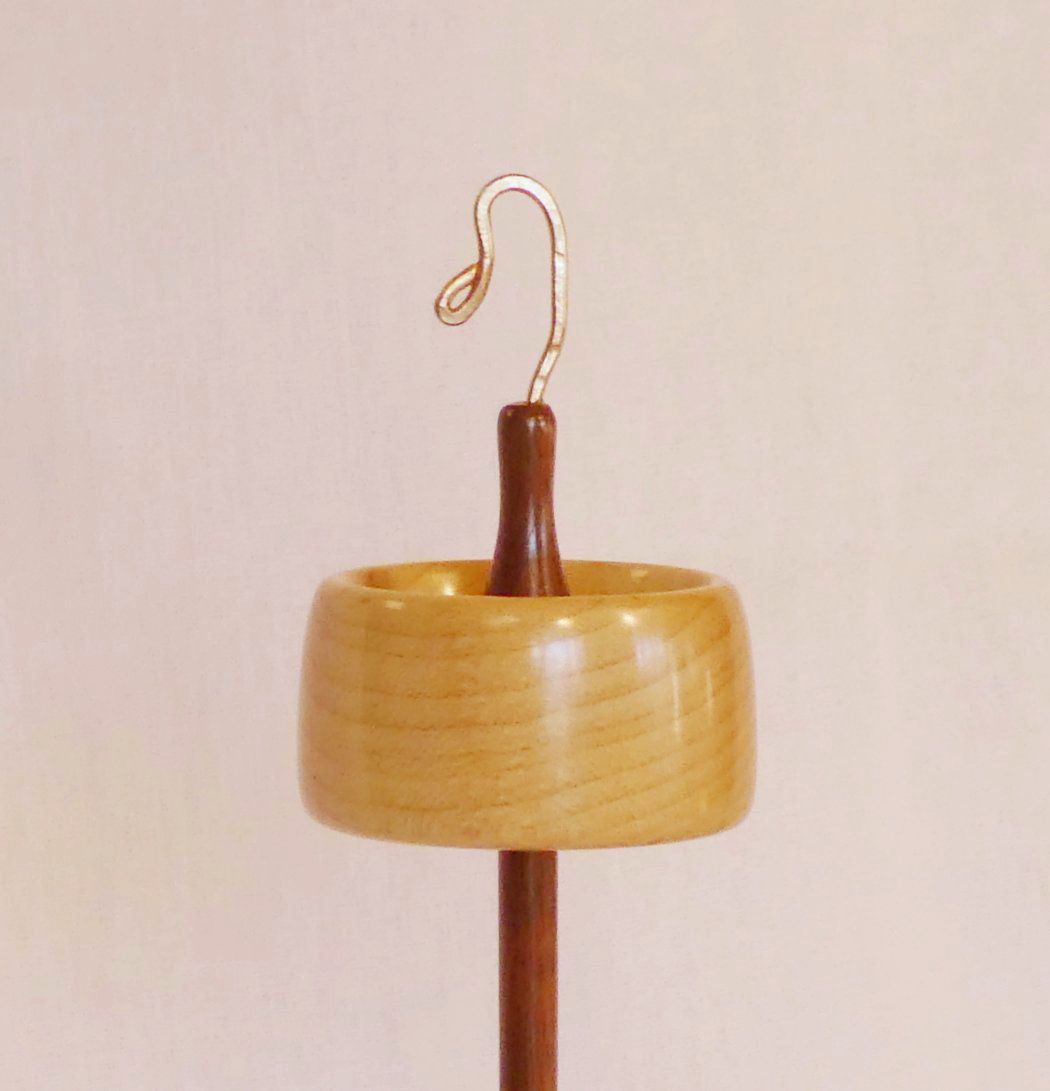 Branch size top whorl drop spindle handmade from Black Walnut and Quilted Maple woods by Cynthia D. Haney. Features a rim weighted whorl shape with a notch and bronze hook.