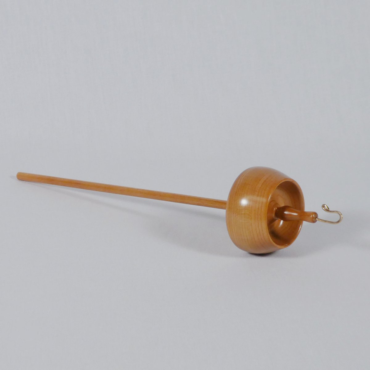 Featuring a deeply hollowed bowl shaped whorl this top whorl drop spindle is rim weighted due to its shaping. Created by Cynthia D. Haney from Cherry wood.