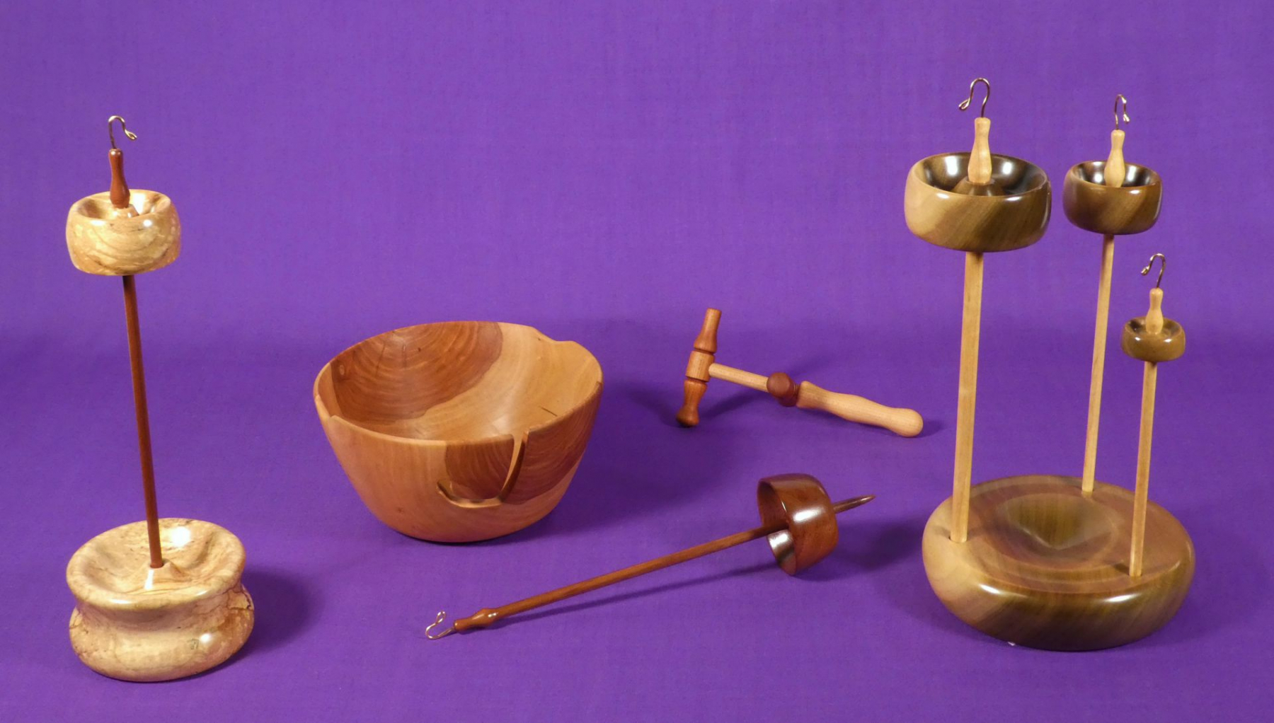 Top whorl drop spindle set with a matching base or display stand, woods ambrosia maple and black walnut. Apple hand turned yarn bowl, cherry mini size niddy-noddy. Branch size bottom, low, whorl spindle to be used supported or suspended in black walnut. Set of trunk, branch, and twig size top whorl drop spindles with matching holder, woods tulip poplar on curly ash. All made by Cynthia D. Haney in her Virginia, USA workshop.