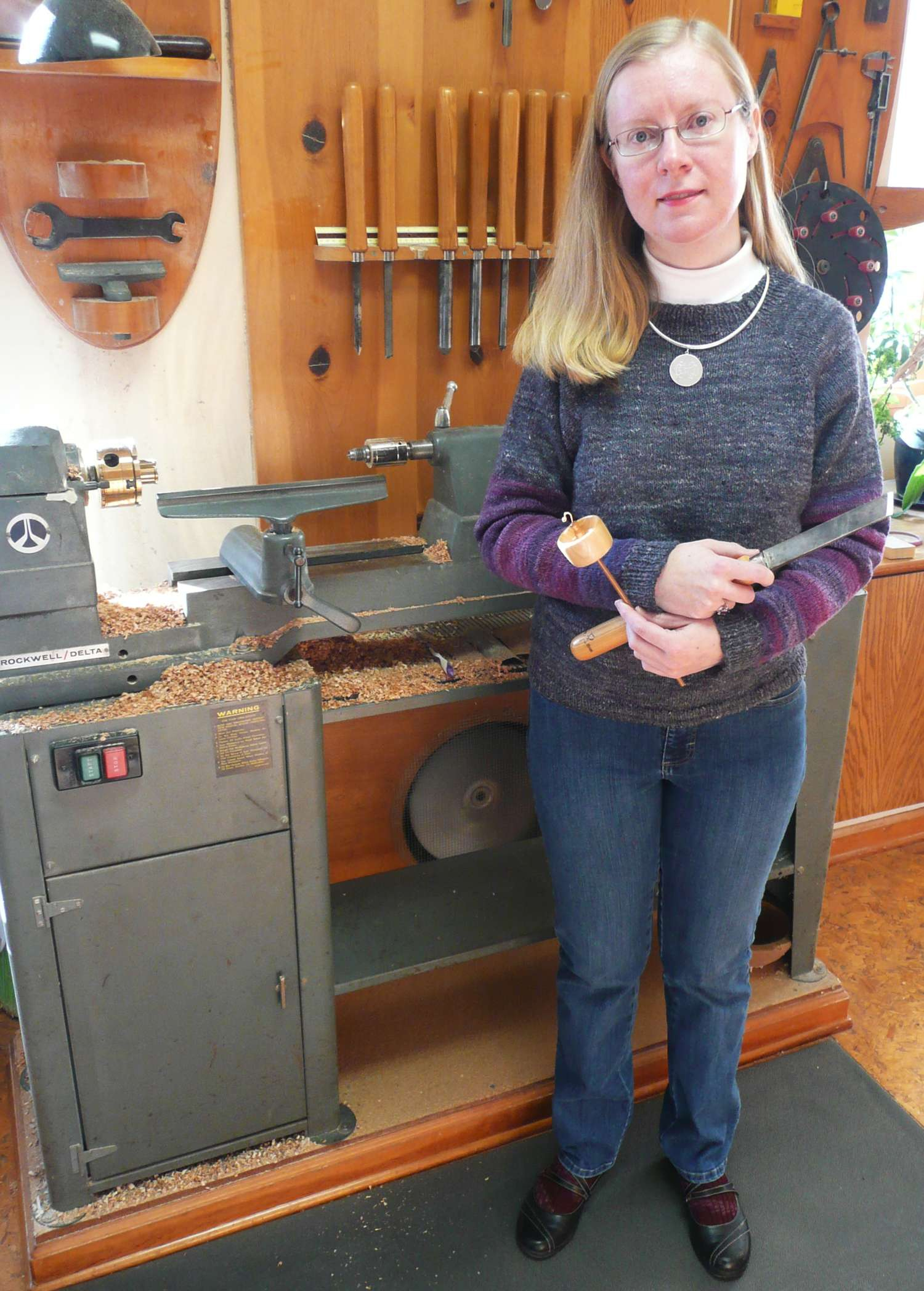 Cynthia Dianne Haney at her wood lathe holding a skew chisel and a top whorl drop spindle.  Showing the spindle maker in her element, wearing a handspun hand knit sweater made entirely with her spindles.