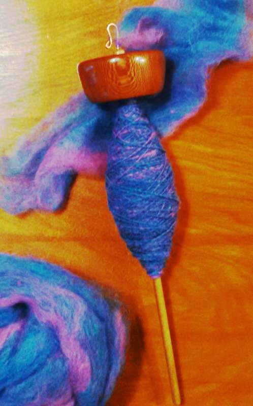 Roving blended in shades of blue, pink, and purple by Kid Hollow Farm.  Being spun into singles on a top whorl drop spindle made by Cynthia D. Haney of Sycamore on a Maple shaft.
