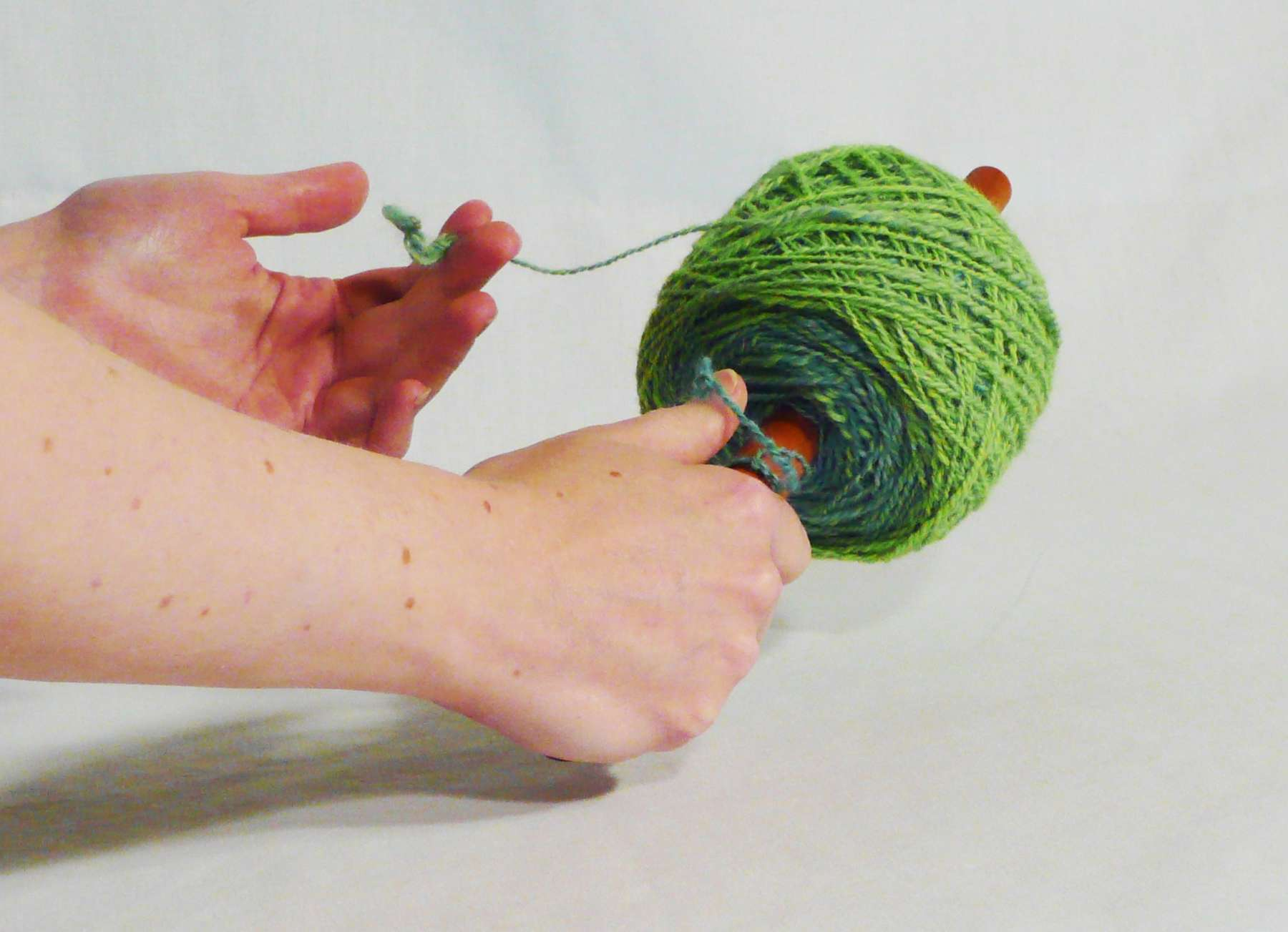 How to use a nostepinne getting from skein to yarn ball, center pull.    On a cherry wood nostepinne hand turned by owner artisan Cynthia D. Haney in her Virginia wood shop.