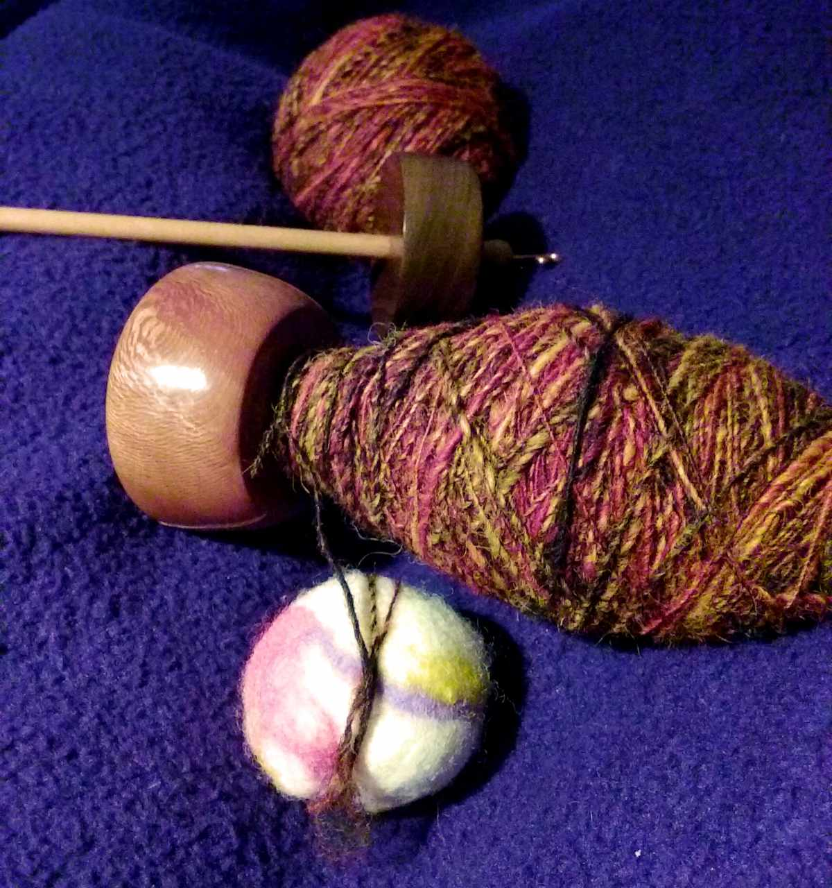 From right a fist sized ball of singles yarn in red yellow and black, high whorl suspended spindle empty lying upside down with a black walnut whorl and a sycamore shaft;  Top whorl drop spindle in Sycamore on Maple with a full oval shaped cop of singles yarn; small felt ball with the end of the yarn from the spindle wrapped around it twice.  all the creative work of Cynthia D. Haney