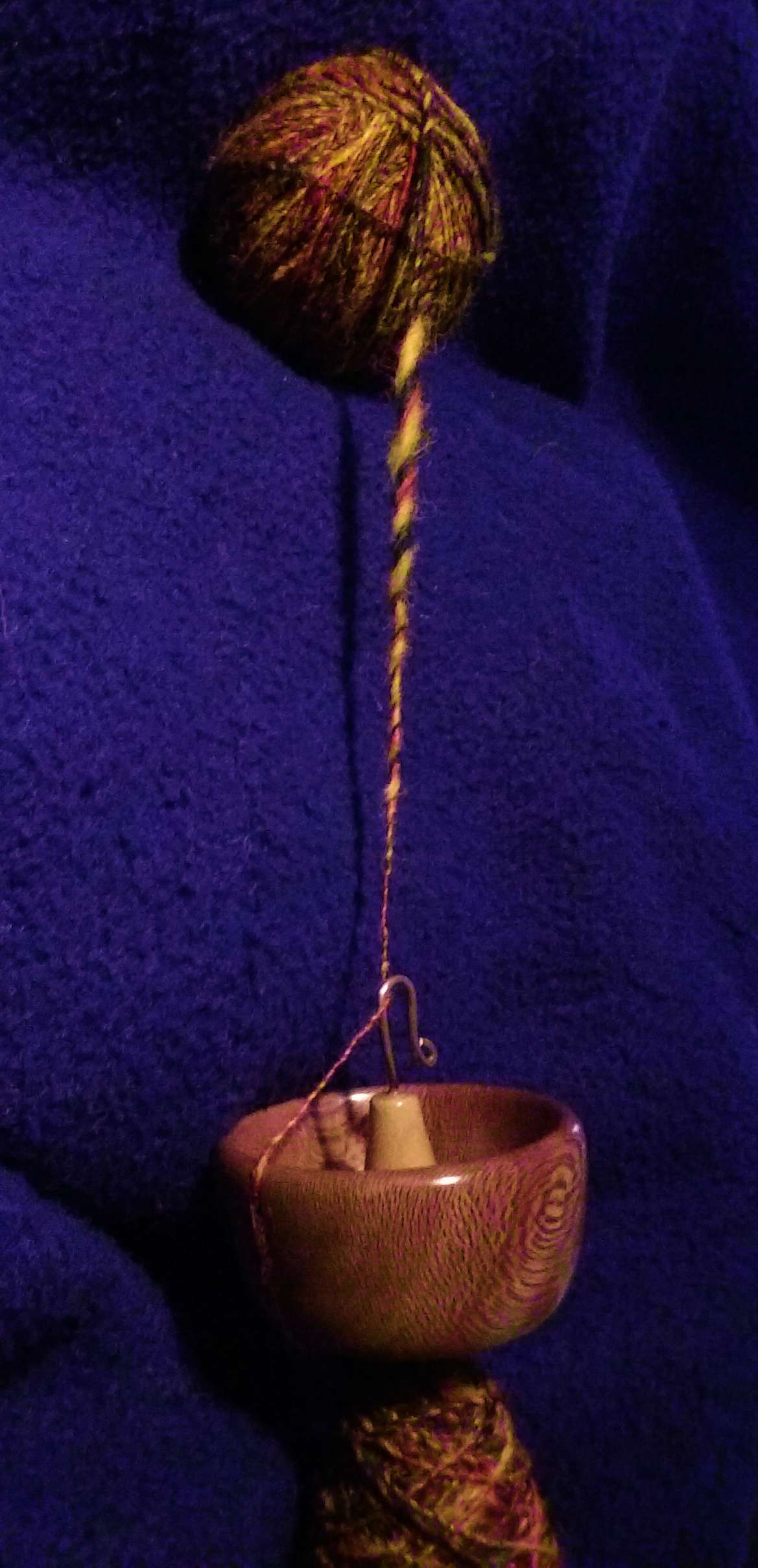 Spindle with single running in the notch to the hook ready to be used in fixing the slub or lump or thick spot in the handspun yarn.  Learn how to master your spinning.