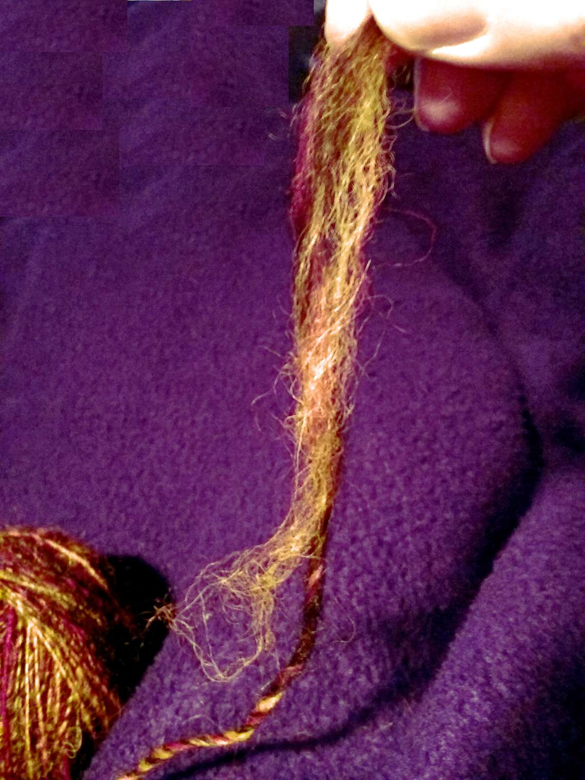Close up of the join between the spindle and the plying ball, in this hand spun single yarn that drifted apart.