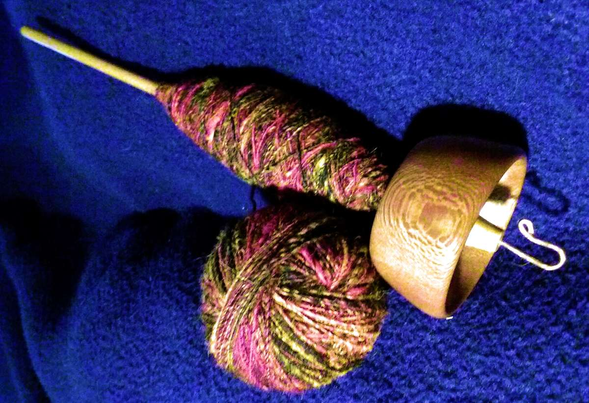 Top whorl drop spindle in sycamore and maple showing how the cop of spun yarn has been shaped on the spindle shaft for stable storage.  Plying ball almost fully wound.  Designed and taught by Cynthia D. Haney