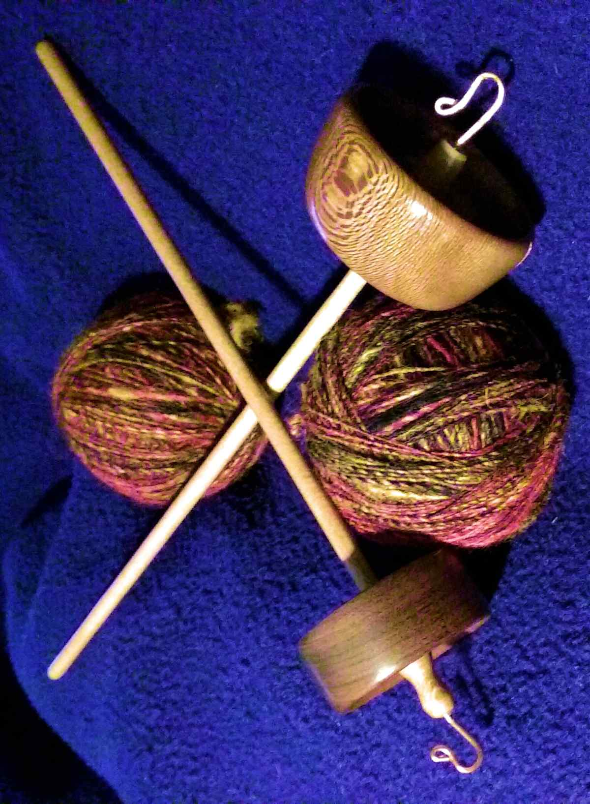 Success both spindles empty of their yarn which is wound into the two plying balls .  Spindles and spinning by Cynthia D. Haney of Cynthia Wood Spinner.  Branch size top whorl one ounce rim weighted drop spindles.