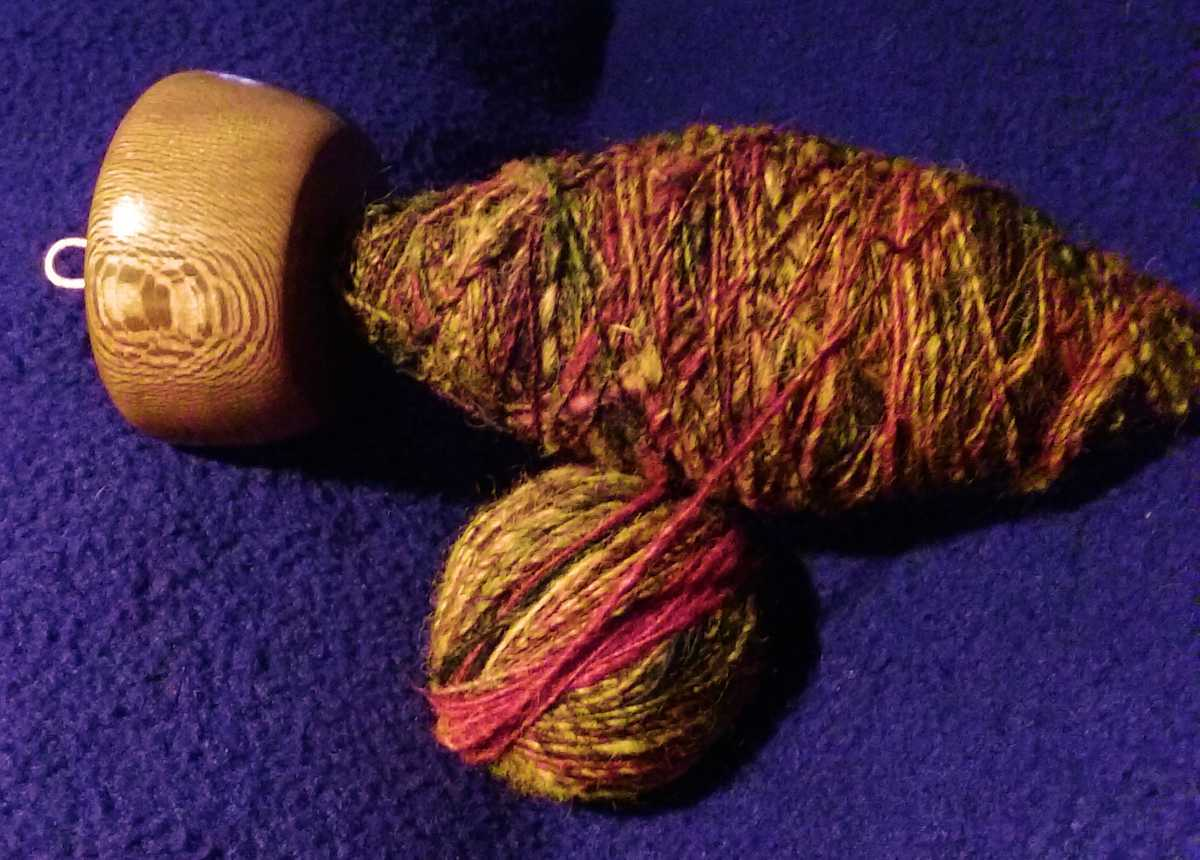 Sycamore wood has neat patterns in the grain making for a beautiful side to this top whorl drop spindle hand turned by Cynthia D. Haney.  The cop of spun yarn is partly transferred to a plying ball.